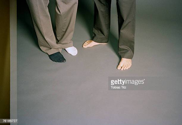 low section of two men standing barefoot - mismatched clothes stock pictures, royalty-free photos & images