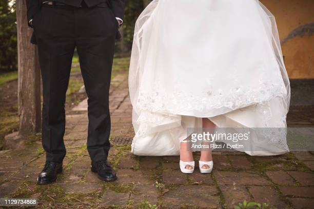 low section of well dressed couple standing on footpath - andrea rizzi stockfoto's en -beelden