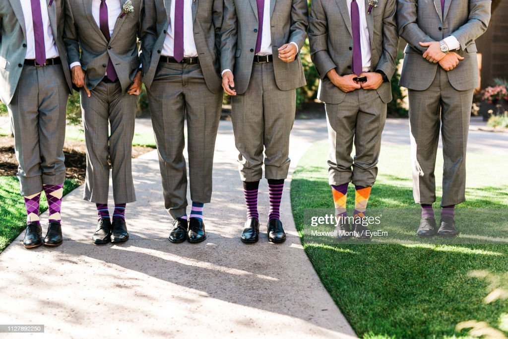 Low Section Of Well-Dressed Groomsmen Standing Side By Side On Field : Stock Photo