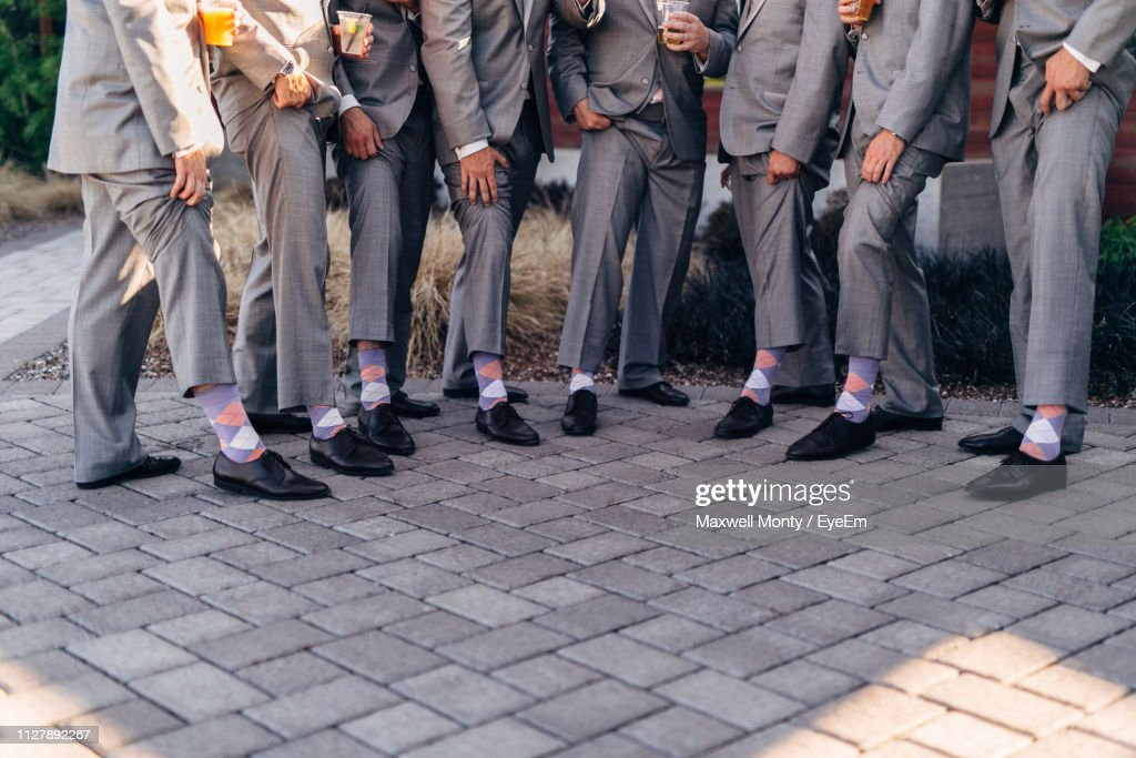 Low Section Of Well-Dressed Groomsmen Standing Side By Side On Footpath : Stock Photo
