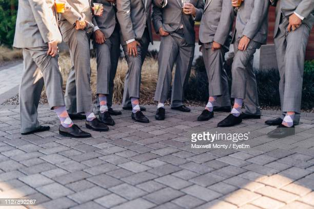 low section of well-dressed groomsmen standing side by side on footpath - monty shadow stock photos and pictures