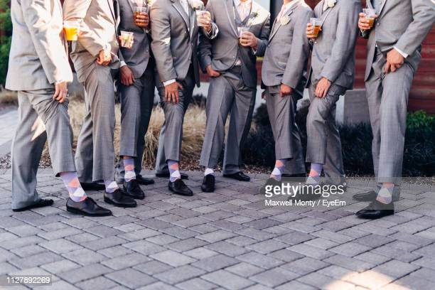 low section of well-dressed groomsmen standing side by side on footpath - monty shadow - fotografias e filmes do acervo