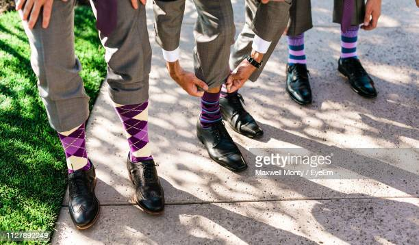 low section of well-dressed groomsmen wearing socks standing on footpath - monty shadow stock photos and pictures