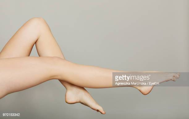 low section of woman against gray background - leg stock pictures, royalty-free photos & images