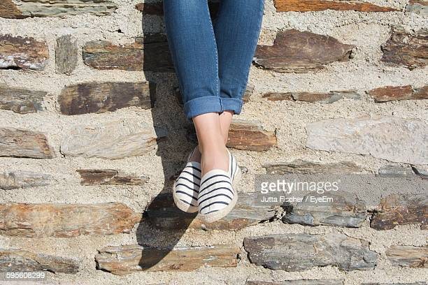 low section of woman against stone wall - rolled up trousers stock pictures, royalty-free photos & images