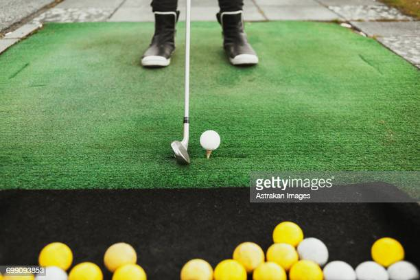 Low section of woman aiming golf ball at driving range