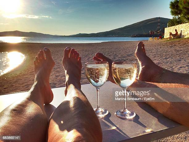Low Section Of Woman And Man By Champagne Flutes At Beach Against Sky