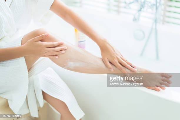 low section of woman applying cream on legs while sitting in balcony - 人の脚 ストックフォトと画像