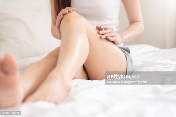 low section of woman applying moisturizer while sitting on bed at home - 人の脚 ストックフォトと画像