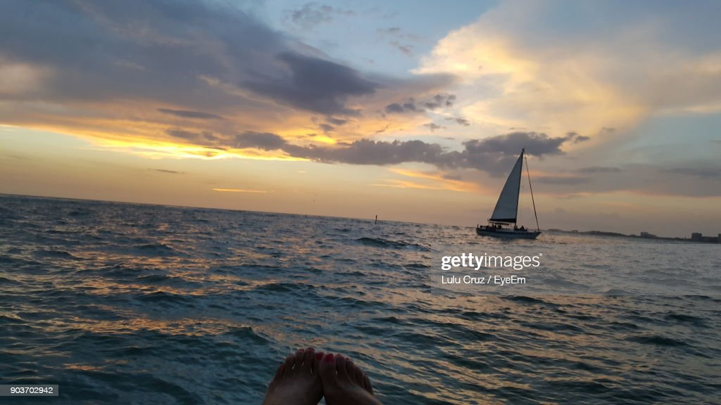 Low Section Of Woman At Beach Against Sky During Sunset : Stock Photo