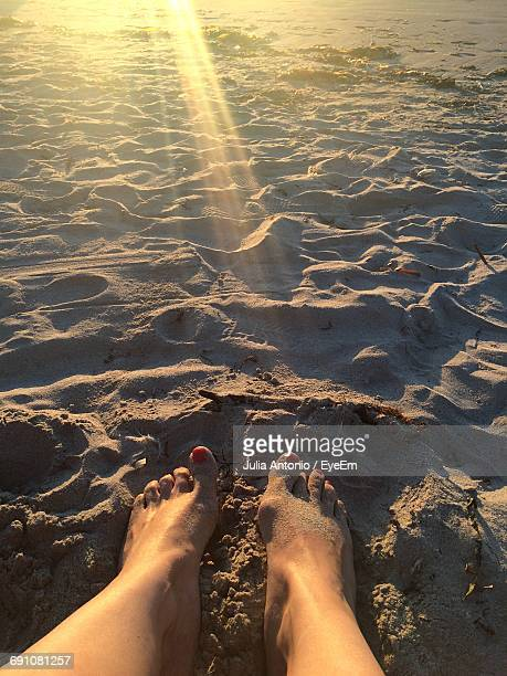 Low Section Of Woman At Beach During Sunset