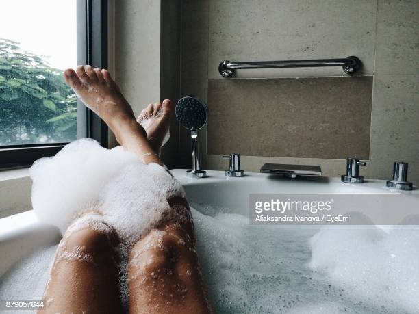 Low Section Of Woman Bathing In Bathtub