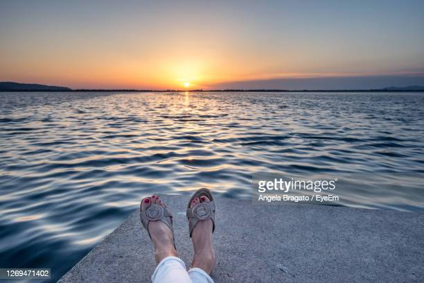 low section of woman by sea against sky during sunset - orbetello imagens e fotografias de stock