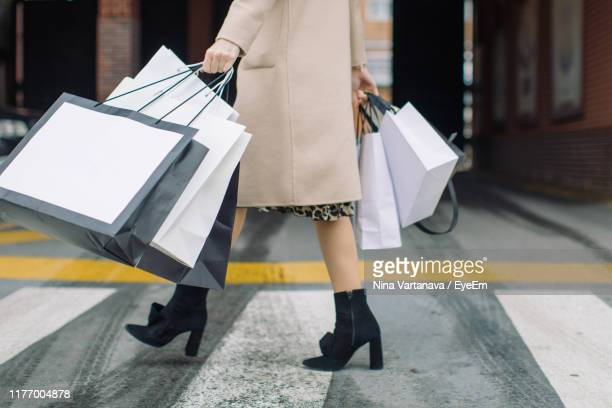 low section of woman carrying shopping bags on zebra crossing in city - shopping bag stock pictures, royalty-free photos & images