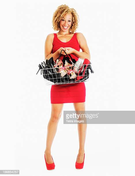 Low section of woman carrying shopping basket with shoes, studio shot