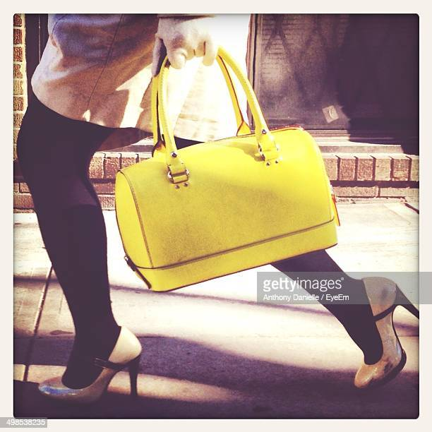 Low section of woman carrying yellow purse