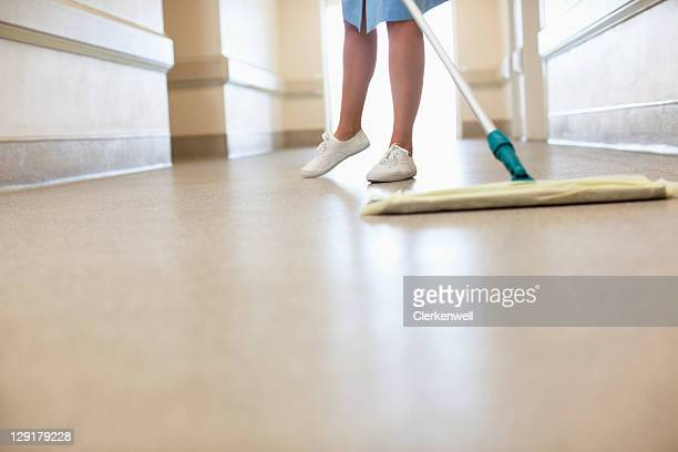 Low section of woman cleaning floor