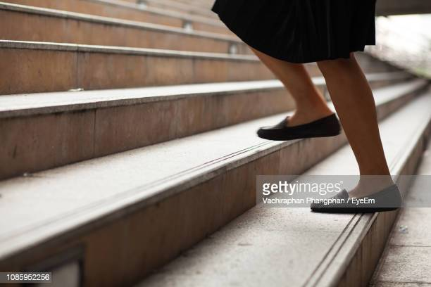 low section of woman climbing on steps - stufen stock-fotos und bilder