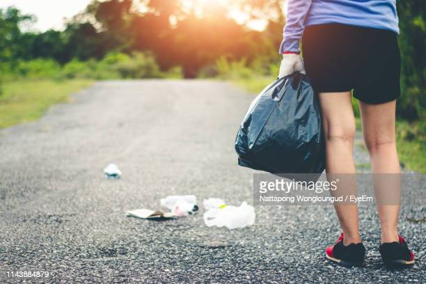 low section of woman collecting garbage on road - city cleaning stock pictures, royalty-free photos & images