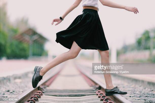 low section of woman crossing railroad track - 人の脚 ストックフォトと画像