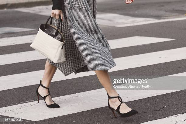 low section of woman crossing road - talons hauts photos et images de collection