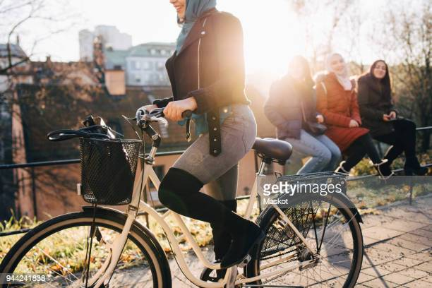 Low section of woman cycling by female friends sitting on railing in city