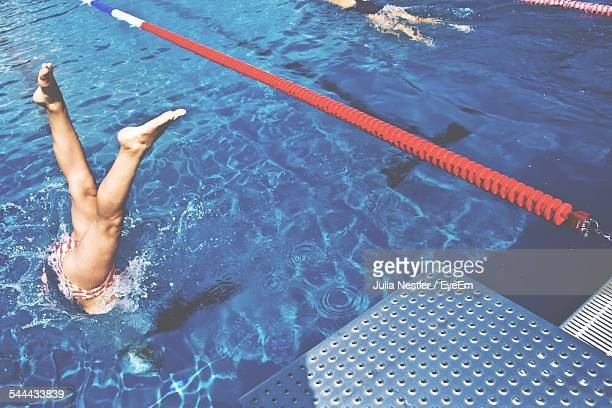 Low Section Of Woman Diving In Swimming Pool