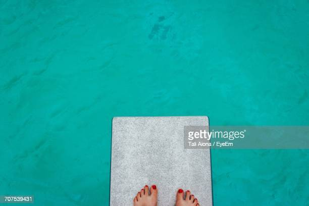 Low Section Of Woman Divingboard Against Swimming Pool