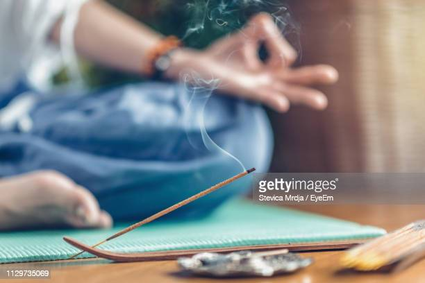 low section of woman doing yoga by burning incense at home - wierook gefabriceerd object stockfoto's en -beelden