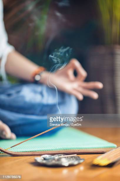 low section of woman doing yoga by burning incense at home - incense stock photos and pictures