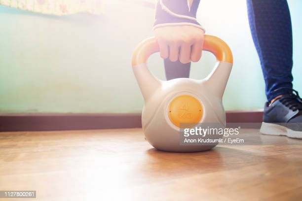 Low Section Of Woman Exercising On Hardwood Floor