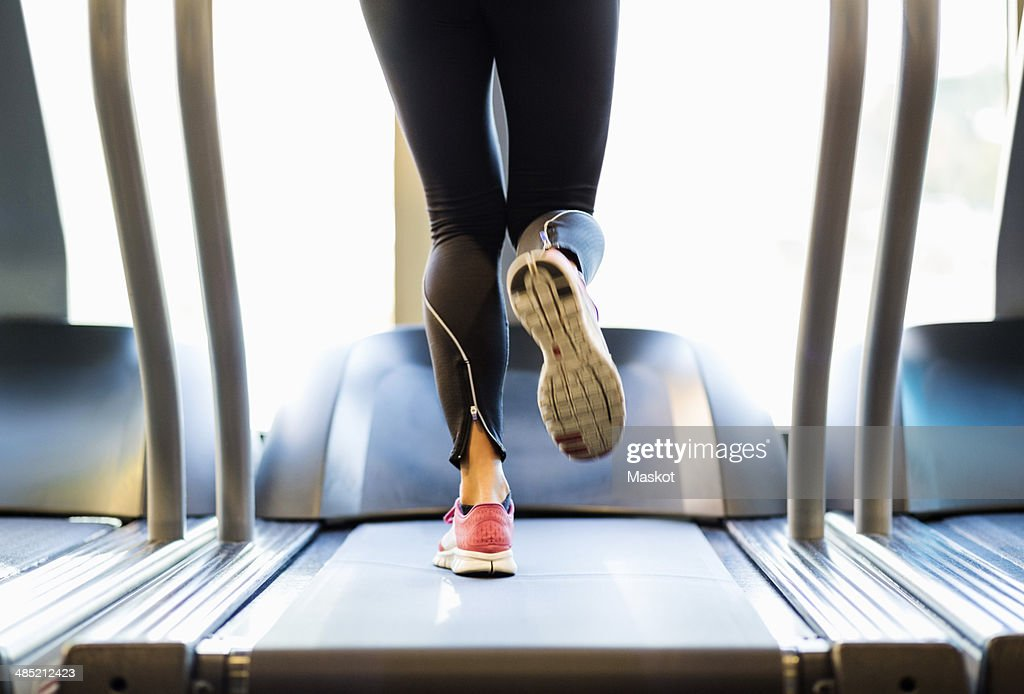 Low section of woman exercising on treadmill : Stockfoto
