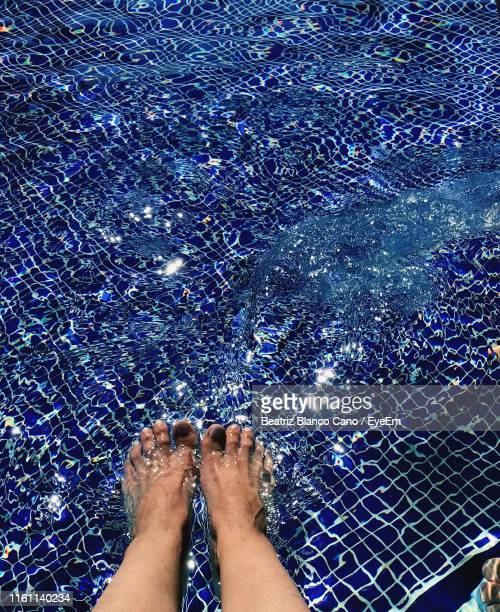 Low Section Of Woman Feet In Swimming Pool