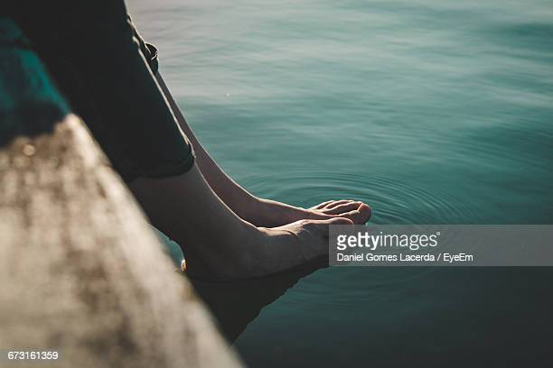 low section of woman feet in water at lake - mujeres fotos stock pictures, royalty-free photos & images