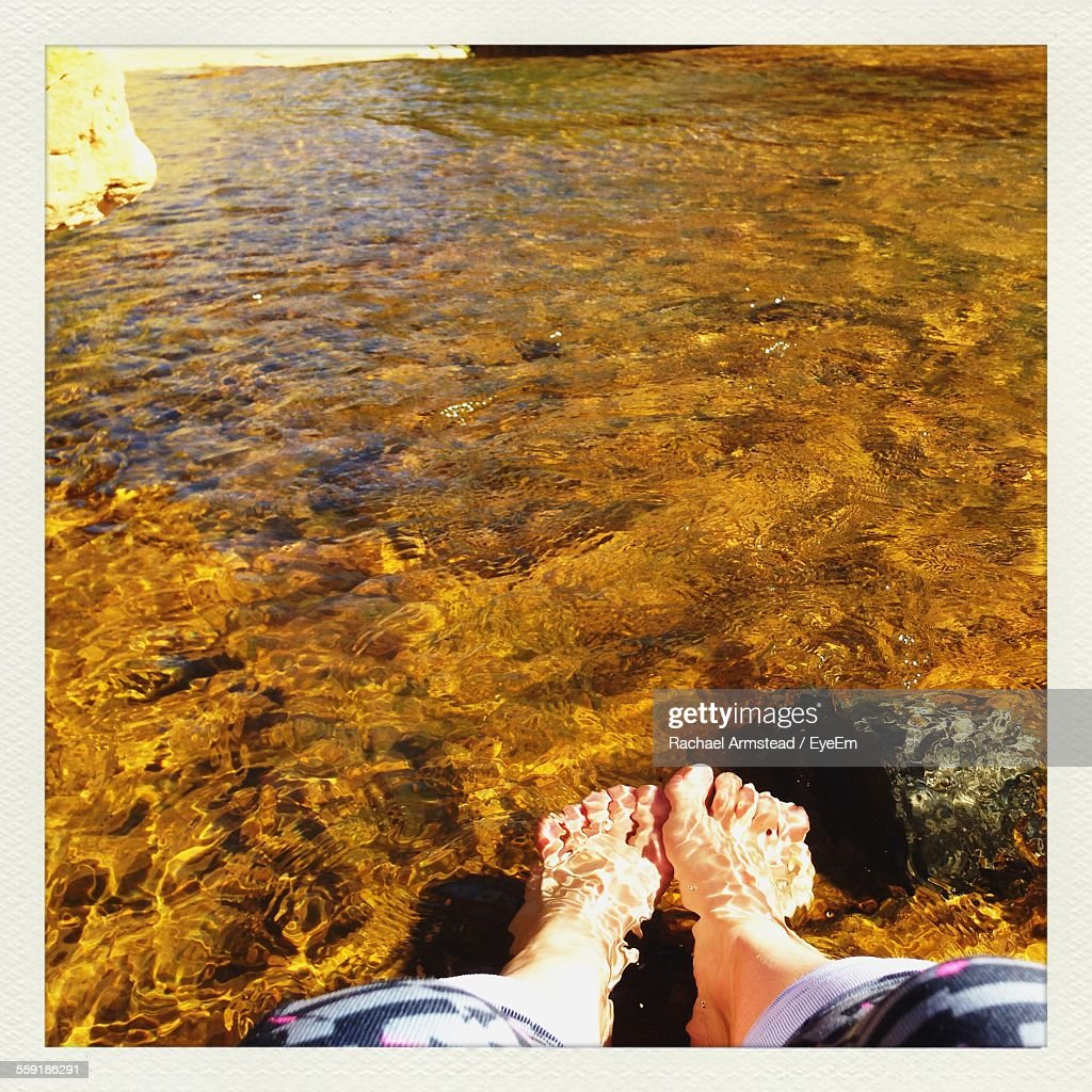 Low Section Of Woman Feet In Water : Stock Photo
