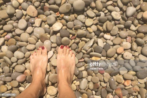 low section of woman feet on pebbles at beach - pebble stock pictures, royalty-free photos & images