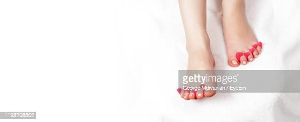 low section of woman having reflexology therapy at spa over white background - reflexology stock pictures, royalty-free photos & images
