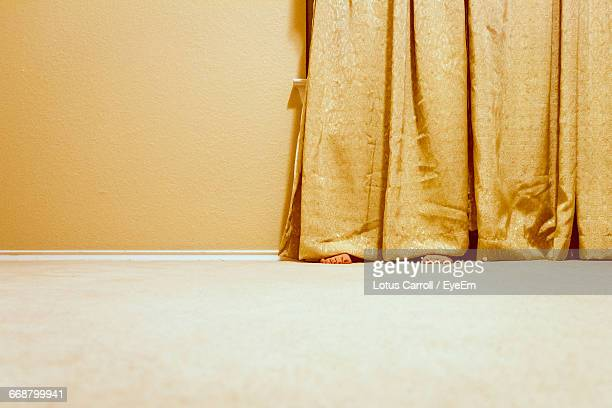 Low Section Of Woman Hiding Behind Curtain At Home