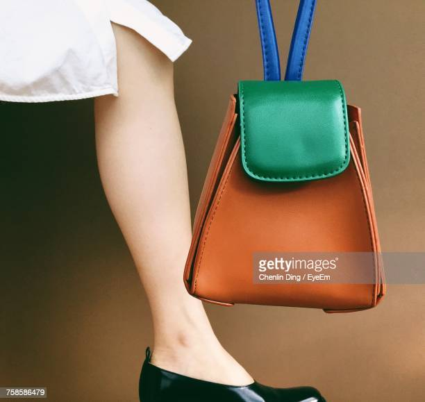 low section of woman holding bag - leather purse stock pictures, royalty-free photos & images