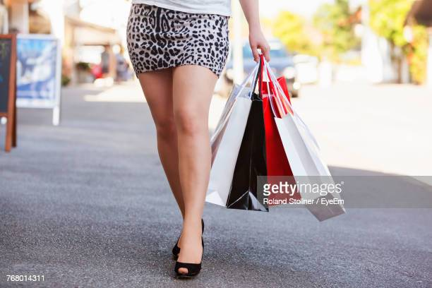 low section of woman holding bags while walking on road - mini jupe photos et images de collection