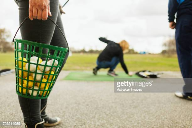 low section of woman holding basket with balls at golf course - driving range stock pictures, royalty-free photos & images
