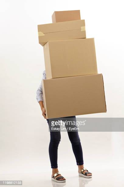 low section of woman holding carton over white background - carrying stock pictures, royalty-free photos & images