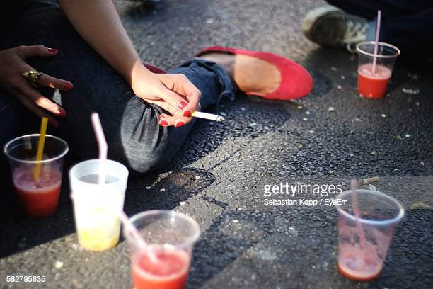 Low Section Of Woman Holding Cigarette While Sitting In Front Of Drinks On Street