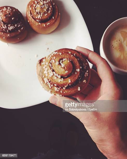 Low Section Of Woman Holding Cinnamon Bun Over Plate