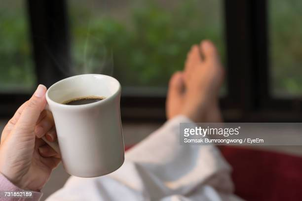 Low Section Of Woman Holding Coffee Cup By Window