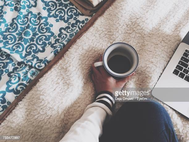 Low Section Of Woman Holding Coffee Cup On Blanket