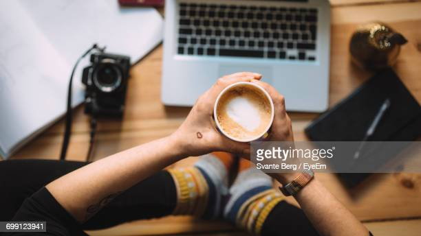 Low Section Of Woman Holding Coffee Cup