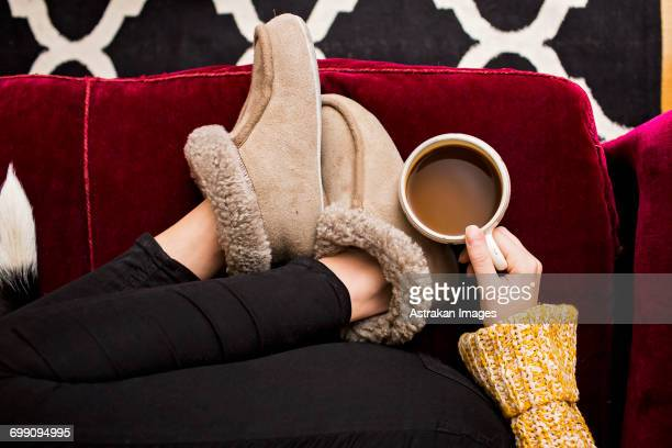 Low section of woman holding coffee cup while sitting on sofa at home