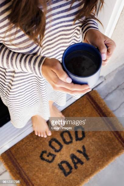 low section of woman holding coffee cup while standing at doorway - human doormat foto e immagini stock