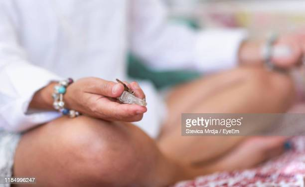 low section of woman holding crystal - alternatieve geneeswijzen stockfoto's en -beelden